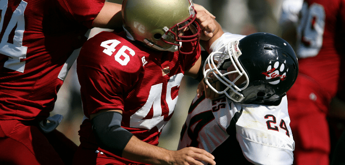 This is an image of American football players grabbing each other during the sport.